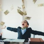 boy in a suit behind a desk throwing cash